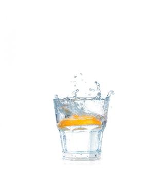 Кубики льда, брызги в стакан воды, изолированные на белом