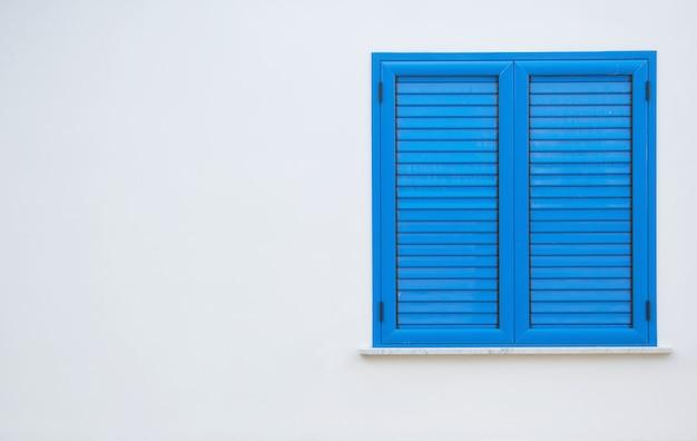 白い壁に青いシャッター付きの窓。閉じたシャッター付きの窓。家の壁の青い窓。