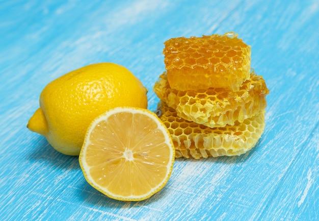 ハニカムとレモンは青い木製の上にあります。