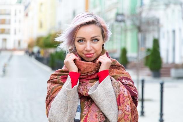Молодая девушка улыбается и укутывается в шарф.