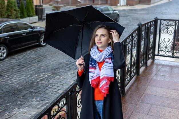 都市通りの傘の下で若い女性