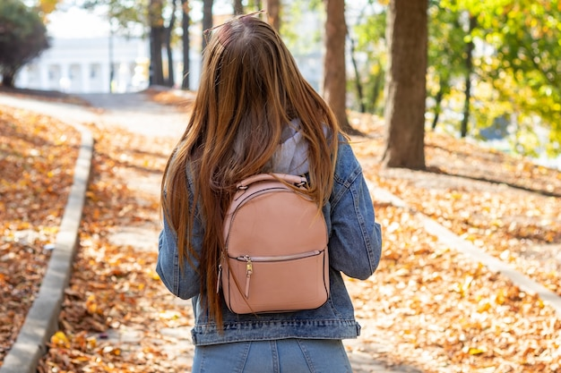 秋の公園で音楽を聴く若い女性