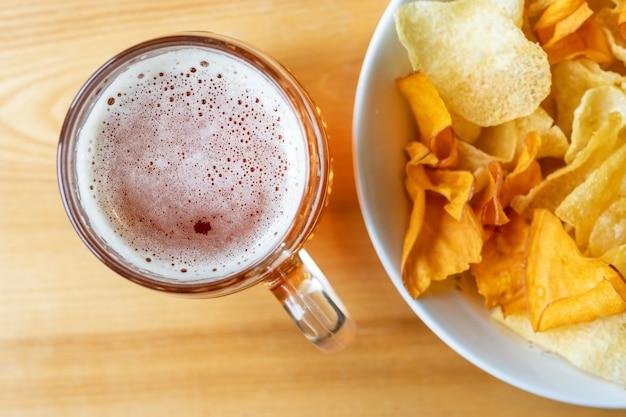 ビールと木製のテーブル上のチップのマグカップ