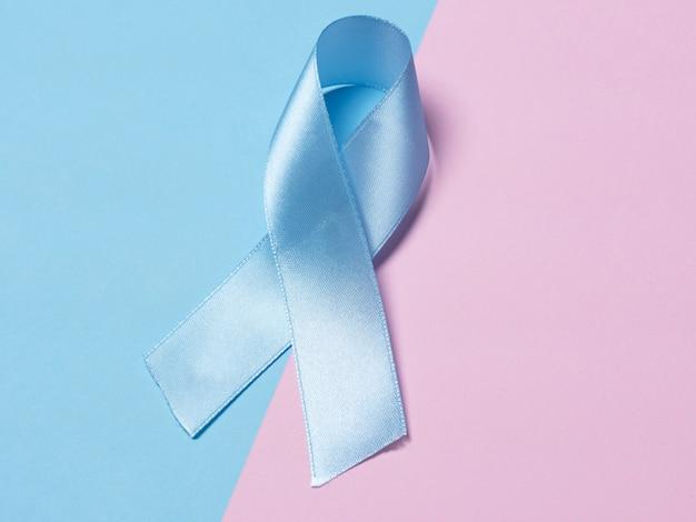 マルチカラーの背景にピンクとブルーのサテンリボンは、前立腺癌の意識のシンボルです。医学の健康管理とがん対策の概念