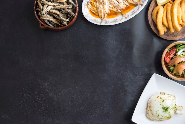 黒の背景に魚の混合(イカ、イワシ、フライ、サーモンのサラダ)