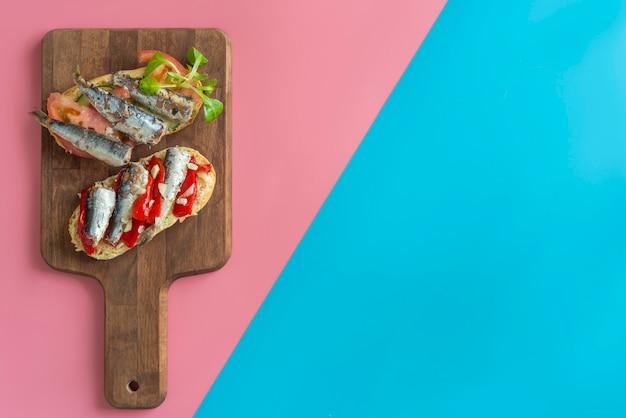 Сардины бутерброд с помидорами, листьями салата, перец,