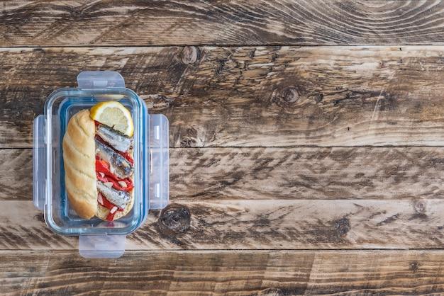 Здоровый бутерброд сардины на деревянном фоне