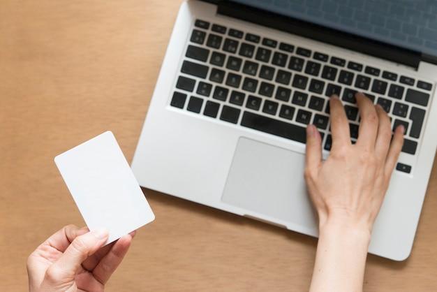 Вид сверху человека с помощью кредитной карты и ноутбука