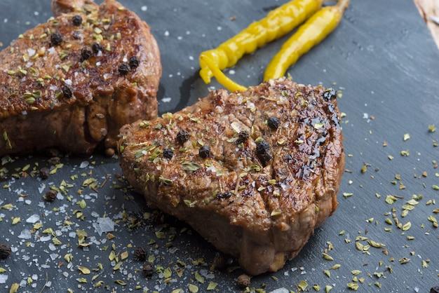 牛肉のグリルステーキ、ローズマリー、塩、コショウ、黒い石のプレート、トップビュー