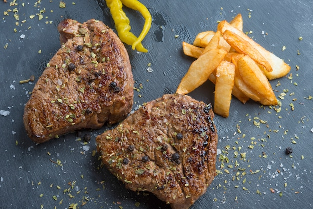 Стейк на косточке на гриле, приправленный специями и свежей зеленью, подается на деревянной доске с картофелем фри и острым зеленым перцем