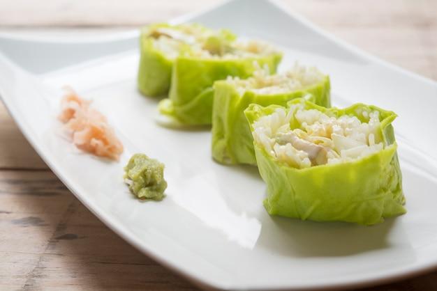 Салат рулет овощной с салатной заправкой в блюде на деревянном для здоровья