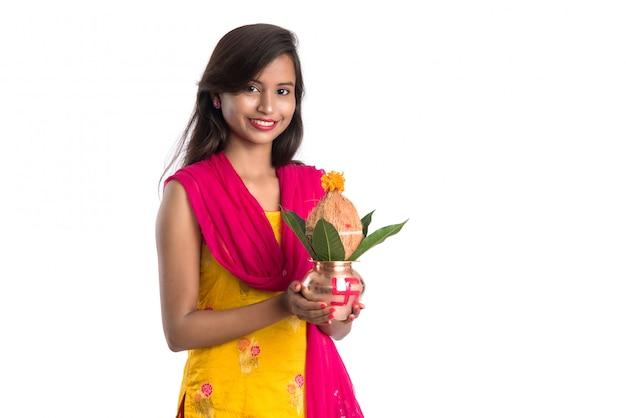 ヒンドゥー教のプージャに不可欠な伝統的な銅カラッシュ、インドの祭り、ココナッツと花の装飾とマンゴーの葉と銅カラッシュを保持しているインドの少女。