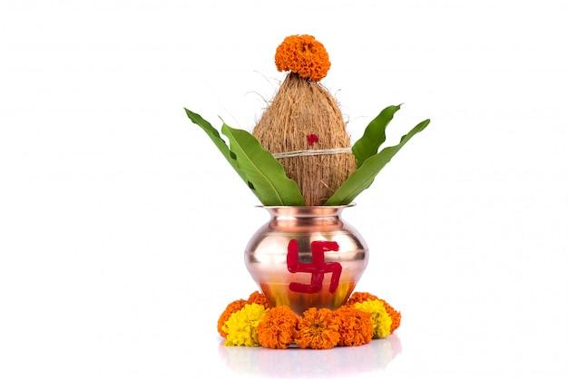 ココナッツとマンゴーの葉と花飾り付きの銅カラッシュ。ヒンドゥー教のプージャに不可欠。