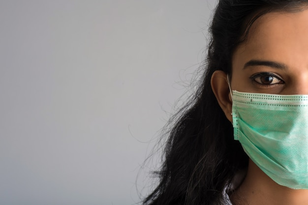 Портрет крупного плана доктора молодой девушки или женщины нося медицинскую или хирургическую маску