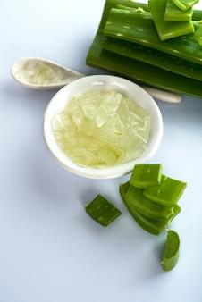 Ломтики алоэ вера оставляют и гель алоэ вера в миске. алоэ вера - очень полезное растительное лекарственное средство для ухода за кожей и волосами.