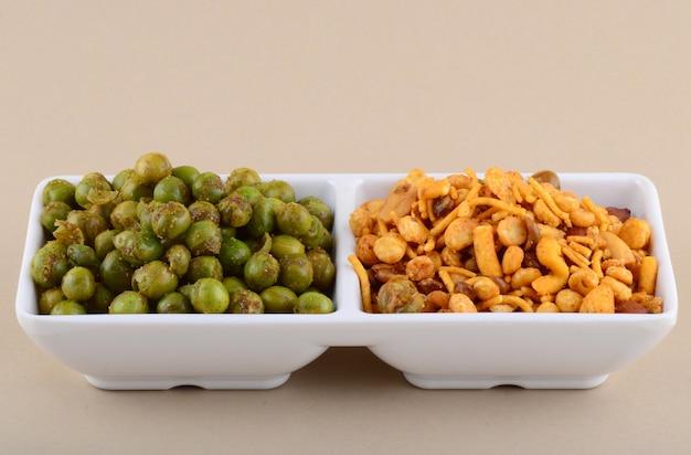 Индийская закуска: смесь и пряный жареный зеленый горошек (чатпата матар) в белой тарелке.