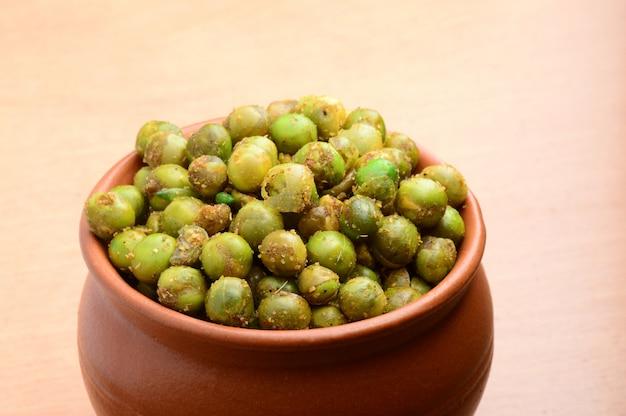 Пряный жареный зеленый горошек (чатпата матар) индийская закуска. сушеный соленый зеленый горошек в глиняном горшочке.
