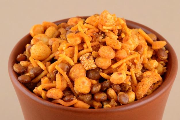 インドのスナック:青のボウルでの混合物(塩コショウマサラ、豆、チャンナマサラダルグリーンピースのローストナッツ)