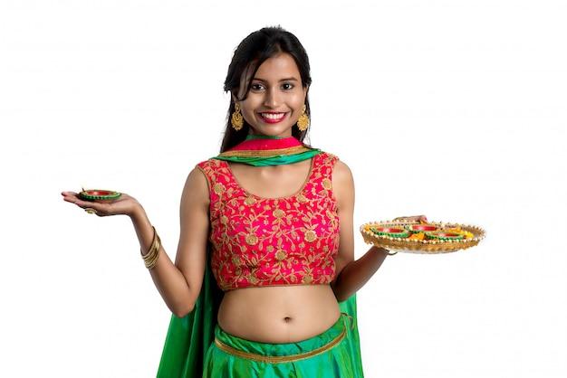 Портрет индийской традиционной девушки, держащей дия, девушку, празднующую дивали или дипавали, держащую масляную лампу во время праздника света на белой поверхности