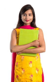 Хорошенькая молодая девушка держит книгу и позирует на белой поверхности