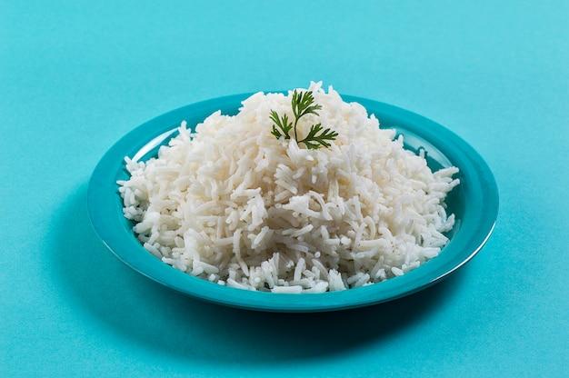 Приготовленный простой белый рис басмати с кориандром в синей тарелке на синей поверхности