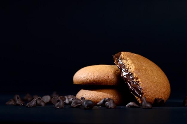 チョコレートクリームが入ったビスケット。チョコレートクリームクッキー。クリーム色の詰物が付いている茶色のチョコレートビスケット