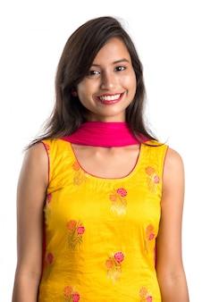 Портрет красивой молодой усмехаясь женщины на белизне.