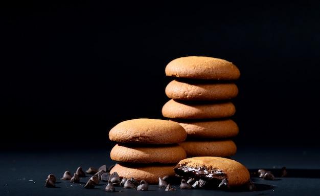 Стопка вкусных кремовых бисквитов с шоколадным кремом на черном