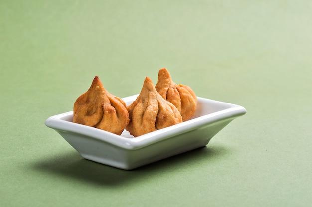 インド料理:緑の空間のモダック、マハラシュトラスウィートディッシュ、主ガネーシャのお気に入りのスウィート、グリーティングカードのデザイン。コピースペース。