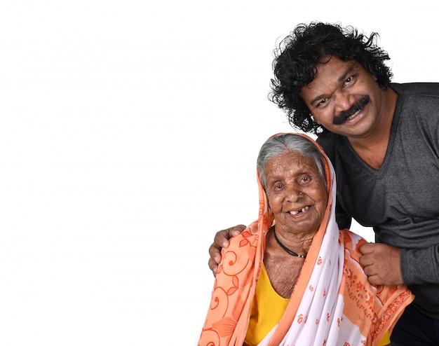 大人の息子と彼の高齢の母親。ホワイトスペースに彼女の息子とインドの年配の女性