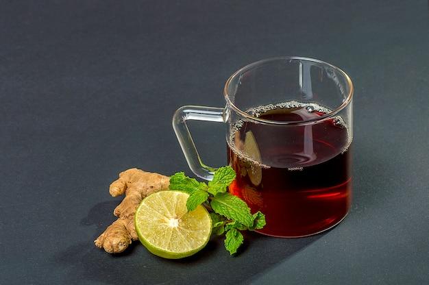 Чашка чая, мяты и лимона на темной поверхности