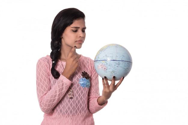 白い壁に分離された地球儀を保持している美しい少女