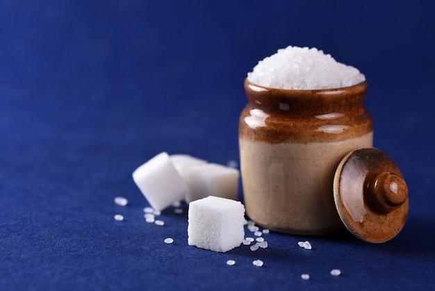 Сахар. белый сахар-песок и рафинированный сахар на синей поверхности