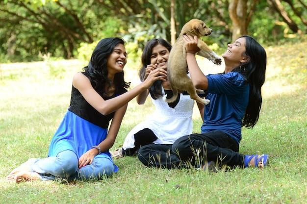 グループの女の子が屋外の公園で子犬と遊んでいます。