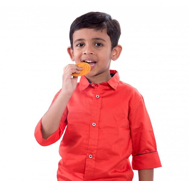 Милый индийский ребенок ест мурукку или чакли на белой стене