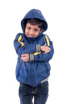白い壁に分離された冬のコートでかわいい男の子