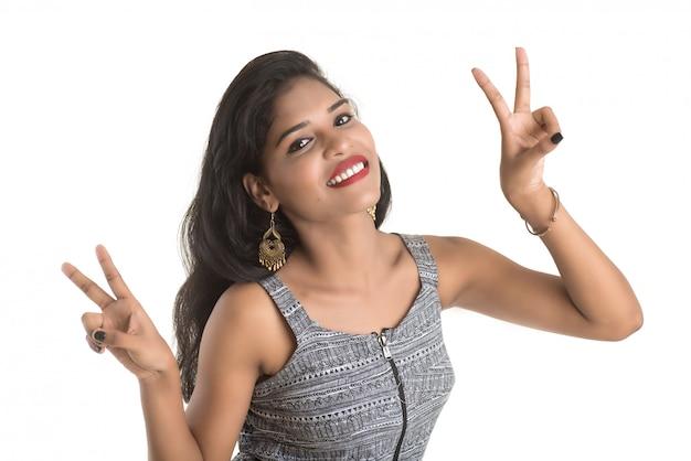 Улыбающаяся веселая девушка показывает знак, изолированные на белой стене