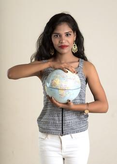 Портрет молодой девушки холдинг и позирует с глобусом.