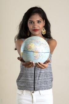Портрет молодой женщины держа и представляя с глобусом мира.