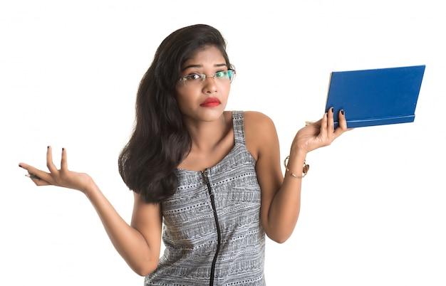 Хорошенькая молодая девушка держит книгу и позирует на белом пространстве