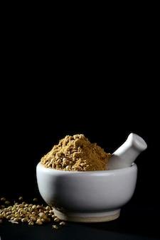 Порошок и семена кориандра с минометом и пестиком на черной предпосылке.