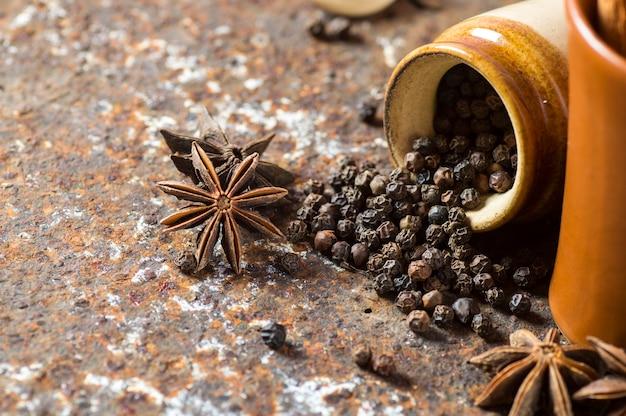 Специи и травы. продукты питания и кухни. палочки корицы, анисовые звезды, черный перец на текстурированном фоне