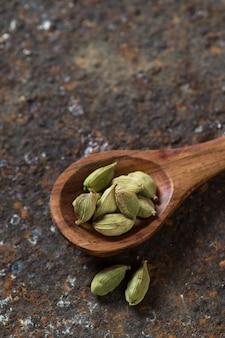 Стручки кардамона в деревянной ложкой на текстурированном фоне