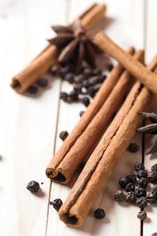 Специи и травы. продукты питания и кухни. палочки корицы, аниса звезды и черный перец на фоне деревянные.
