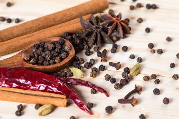 Специи и травы. продукты питания и кухни. палочки корицы, аниса, черный перец, перец чили, кардамон и гвоздика на деревянном фоне