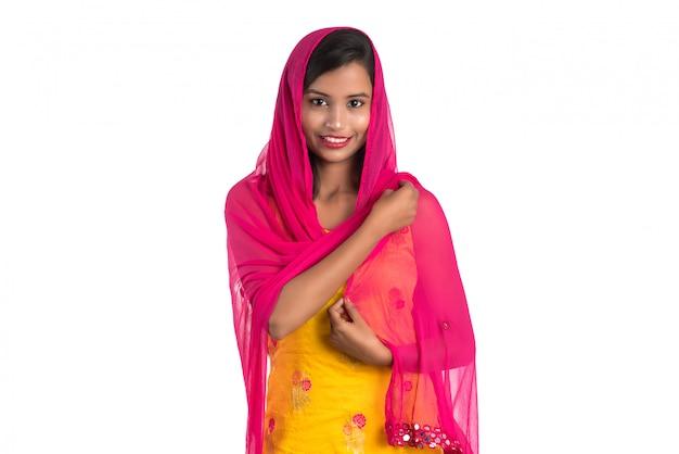 Красивая индийская традиционная девушка представляя на белой предпосылке.