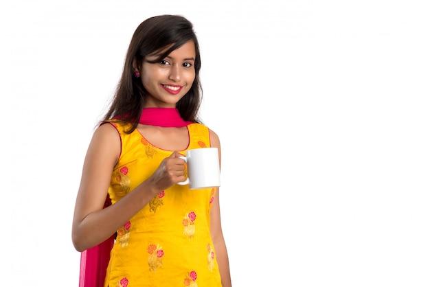 Хорошенькая молодая девушка с чашкой чая или кофе позирует на белом фоне