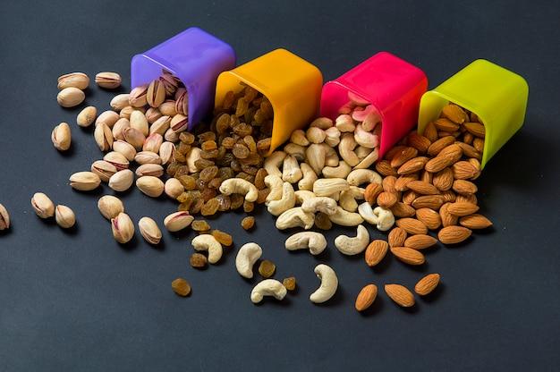 健康的なミックスドライフルーツとナッツの暗い背景。アーモンド、ピスタチオ、カシューナッツ、レーズン