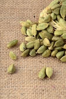 Зеленые стручки кардамона на мешковине
