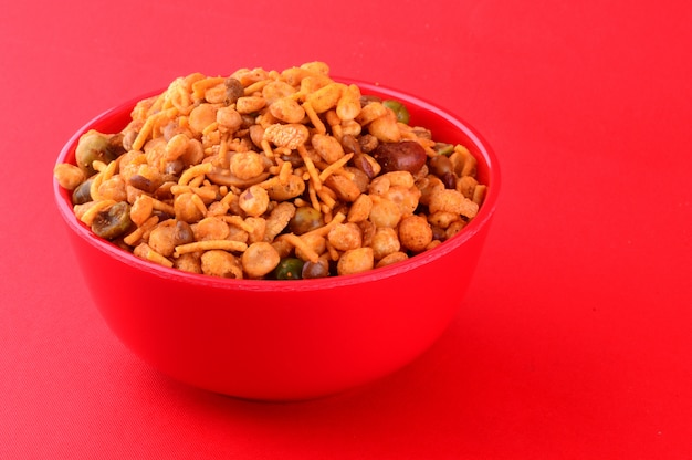 インドのスナック:赤いボウルでの混合物(塩コショウマサラ、豆、チャンナマサラダル、グリーンピースのローストナッツ)